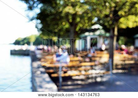 defocused bokeh background. people sitting in beergarden at lake.