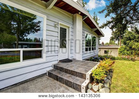 Front Entry Door Of American Siding House With Tile Floor Porch.