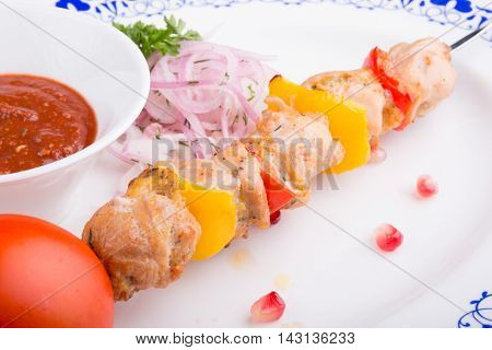Grilled chicken meat on a skewer with vegetables