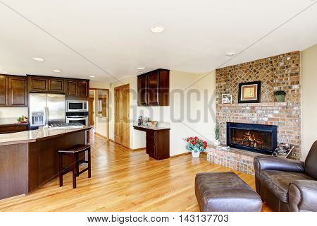 Open Floor Plan Kitchen And Living Room With Brick Fireplace.