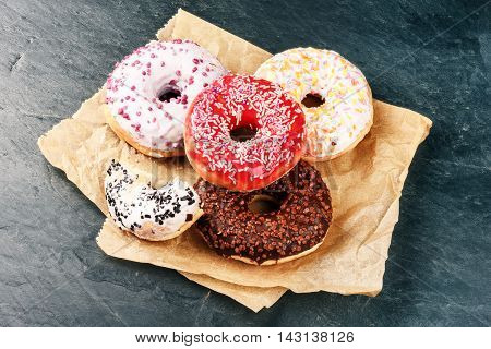 Donuts glazed with various sprinkles on dark blue background. Top view