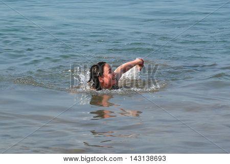 Happy beautiful girl swims in the sea