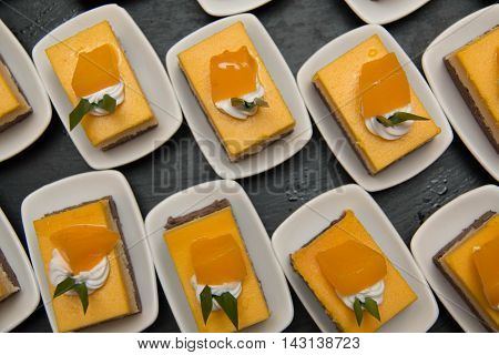 A cut mini orang cheese cake in mni white cup