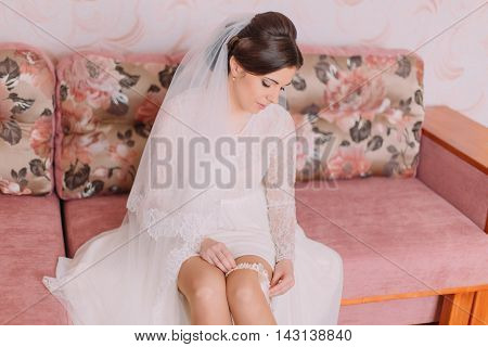 Beautiful bride sitting on sofa in dressing room is wearing bridal garter, preparing herself for wedding ceremony.