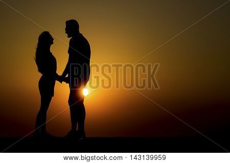 At sunset happy and in love couple of young women and young men.