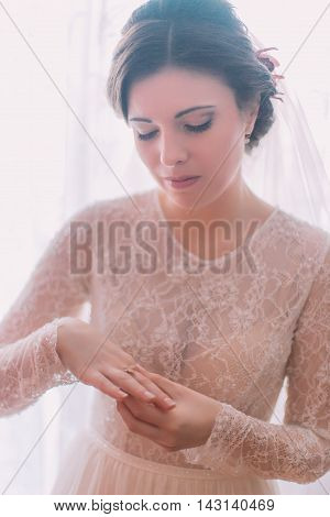 Beautiful brunette bride dressing engagement ring in preparations for wedding.