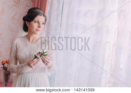 Half-length portrait of beautiful pensive bride in wedding dress near window holding boutonniere.