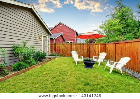 Fenced Backyard Patio With Opened Red Umbrella , Well Kept Lawn