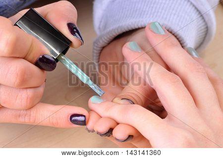 Nail salon - Applying green nail polish on female fingers.