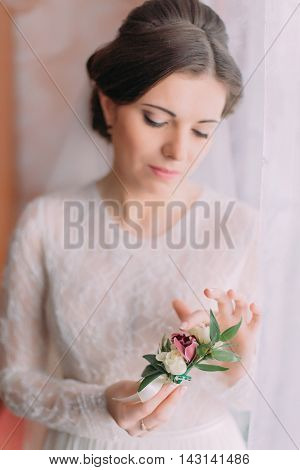 Close-up portrait of beautiful innocent bride in wedding dress near window holding cute boutonniere.