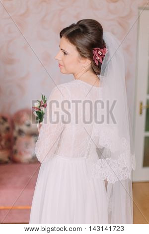 Half-length portrait of beautiful bride in wedding dress looking over her shoulder indoors holding boutonniere.