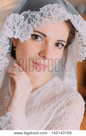 Close-up portrait of beautiful sensual bride in wedding gown with lifted veil and touching her face.