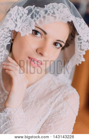 Beautiful sensual bride in wedding gown with lifted veil touching her face while posing indoors.