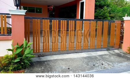 rolling security gate with alternating boards and steel bars in threes, with peach colored posts and house, Songkhla, Thailand