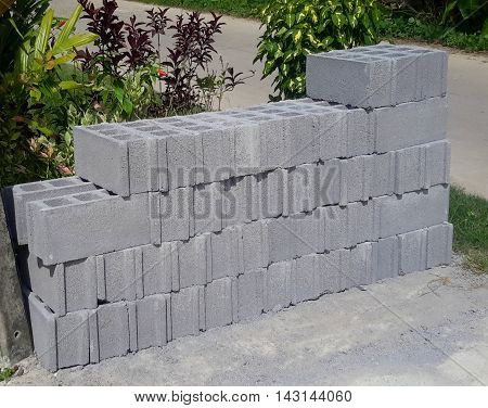 Stack of gray concrete building blocks outside a hardware store next to shrubbery,  Songkhla, Thailand
