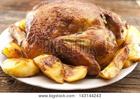 Whole Roasted Chicken With Potatoes On Rustic Wooden Table. Selective Focus.