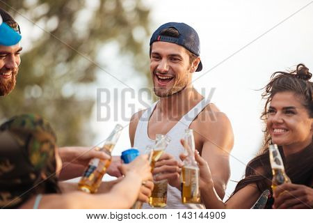 Cheerful young man laughing and celebrating with friends outsoors