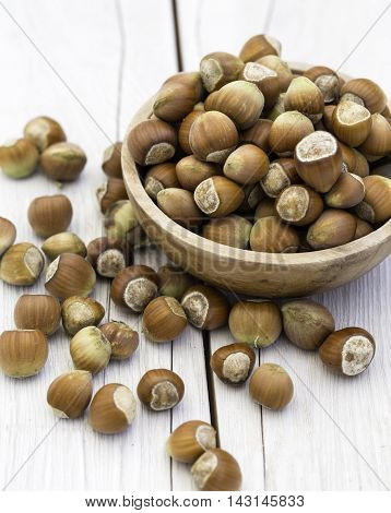 Bowl of fresh hazelnuts on wooden background