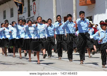 Magdalena Cajamarca Peru - July 25 2016: Group of young Peruvians in blue traditional costumes marches in town parade in Magdalena Cajamarca Peru on July 25 2016