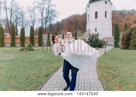 Passionate newlywed pair happily walking in beautiful green park. Loving groom hold his new wife on hands.