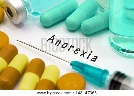 Anorexia - diagnosis written on a white piece of paper. Syringe and vaccine with drugs.