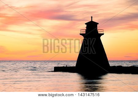 Lake Huron lighthouse silhouetted against a beautiful sunset.