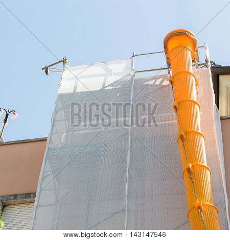 Scaffolding covered with modular slide for debris and rubble