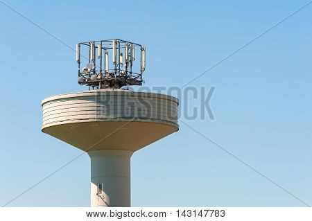 Water Tank Tower Surmounted With A Telephone Repeater Antennas