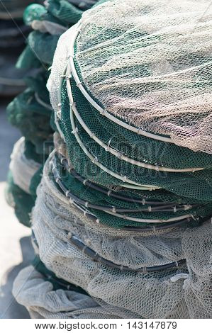 Pots in nylon mesh suitable for fishing in the lagoon piled on the pier