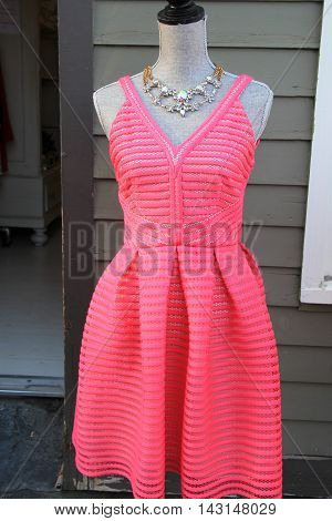 Beautiful pink handcrafted dress on mannequin with pretty costume jewelry necklace.