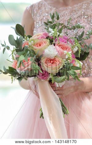 Bride holding a beautiful bridal bouquet. Wedding bouquet of peach roses by David Austin single-head pink rose aqua eucalyptus ruscus gypsophila
