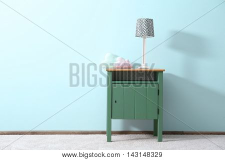 Green bedside table with toys on blue wall background