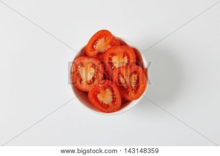 Fresh halved tomatoes in white bowl