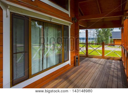 veranda with table wooden house in the forest on a green grass