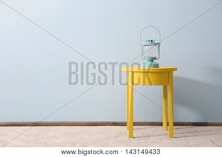 Yellow bedside table with lantern on blue wall background