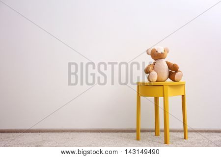Yellow bedside table with toy on white wall background