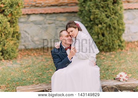 Happy newlywed couple in autumn park. Elegant bride sitting on knees of her handsome new husband.
