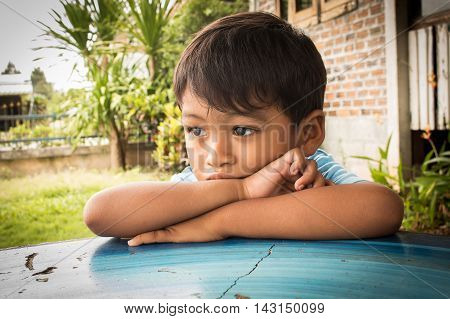 Little boy sad and worried lying on the table in the park