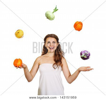 Beautiful young woman juggling fruits and vegetables, isolated over white background