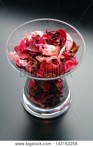 Dried red rose petals in a glass vase on gray background