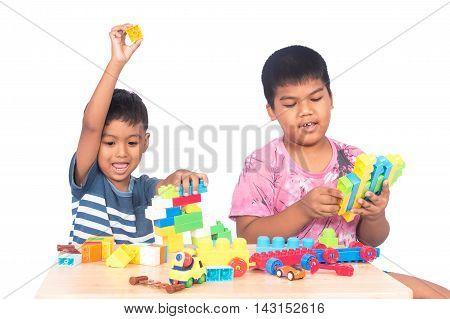 Two cute little boy play building brick