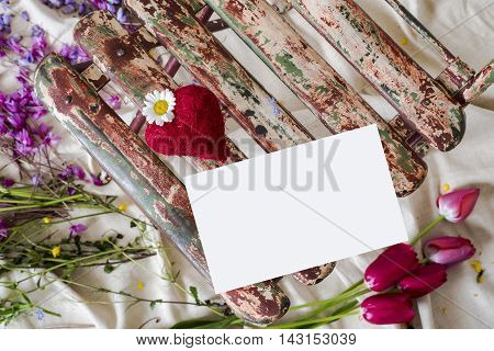 heart with daisy on an old chair in iron, with letter of love, with colorful flower background,
