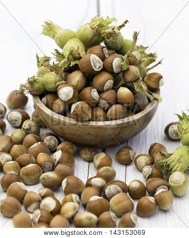 Bowl of fresh hazelnuts on wooden the background
