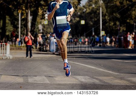 young male athlete running on a city street during marathon