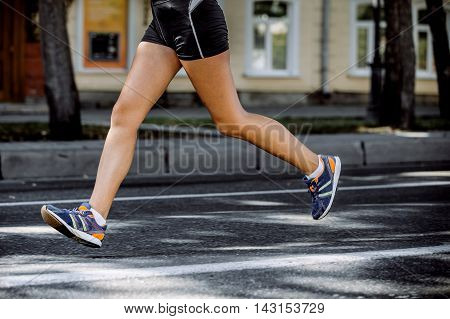 feet young girl athletes running through city streets during marathon