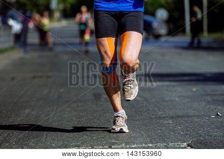 knees kinesio taping male athlete running marathon