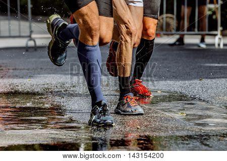 legs of three male marathon runners water splashes from under running shoes