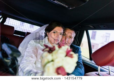 Portrait of happy newlywed couple in car after the wedding ceremony.