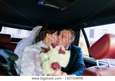Portrait of happy newlywed couple in wedding car after the ceremony.