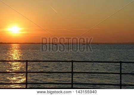 Sunset at Brightlingsea in Essex with the river boats and buildings blurred in the background. Railings in focus in the foreground. Sunset reflected in the water.